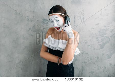 Mime actress performing with mobile phone