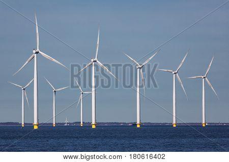 Offshore farm windturbines near Dutch coast against blue sky