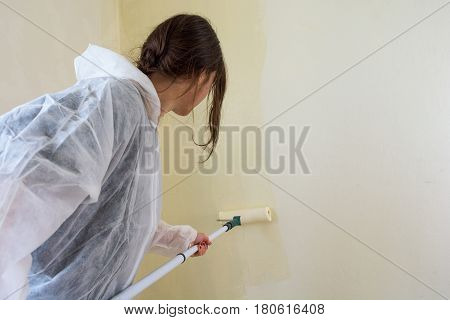 Young female student painting her room. Millenial redecorating.