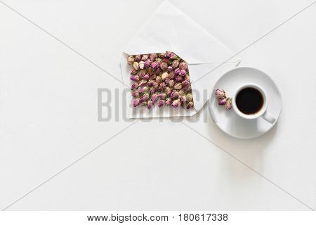 Purple dry roses in envelope and cup of tea on white background, flat lay, overhead view, backgroung mock up