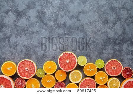 Different citrus fruit frame on dark grey concrete table. Fruit food background. Healthy eating and diet. Antioxidant, detox, dieting, clean eating, vegetarian, fitness or healthy lifestyle concept