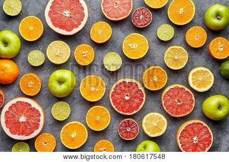 Organic fruit food background. Citrus fruit pattern on grey concrete table. Healthy eating and diet. Antioxidant, detox, dieting, clean eating, vegetarian, vegan, fitness or healthy lifestyle concept