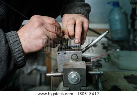 Mechanics repairing a diesel injector. Mans hands disassemble a injector pinched in a vise.