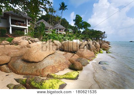 White tourist houses on берегуморя big stones. Sea surf. Green trees and sandy coast.