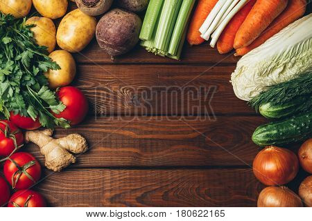 Different vegetables on old wooden table, top view with space for text or recipe. Healthy eating background. Frame of vegetables. Toned