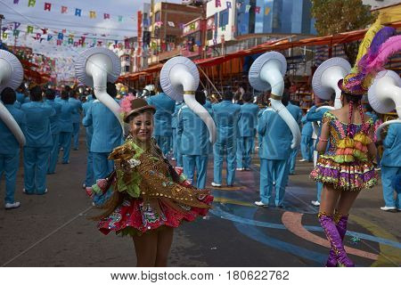 ORURO, BOLIVIA - FEBRUARY 26, 2017: Band of a Morenada dance group in colourful outfits parading through the mining city of Oruro on the Altiplano of Bolivia during the annual Oruro Carnival.