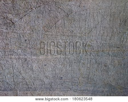 Old stone background texture. Cave wall rusty pattern scratched with marks. Grey ancient rock with blue levels or stripes relief structure.