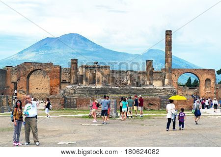 POMPEII, ITALY - MAY 13, 2014: The Temple of Jupiter with Vesuvius in the distance. Pompeii is an ancient Roman city died from the eruption of Mount Vesuvius in 79 AD.