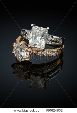 Two jewelry rings with big diamonds on black