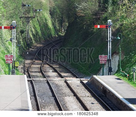Tracks on a heritage railway line in the UK. Semaphore signals are displayed and the line is double tracked at the station with two platforms.
