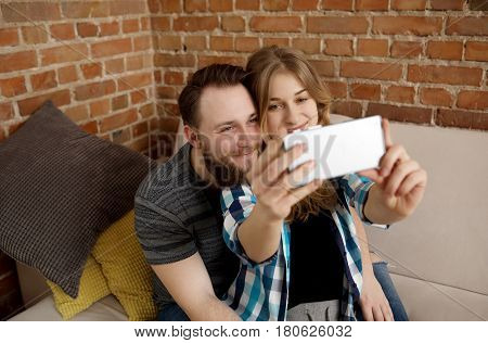 Young lovers couple making photos themself. In home.