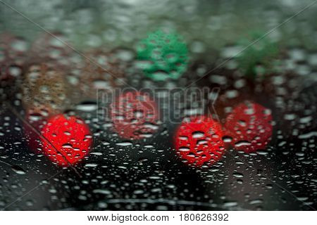 View of the night city through the window on a rainy night, raindrops fall on the windshield of the car. Concept life of a modern city. Abstract background of urban city in night with light bokeh
