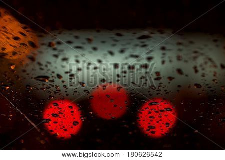 Night lights of urban traffic seen through the windshield in rainy weather. Abstract background for banner design. Concept of night city life and cars