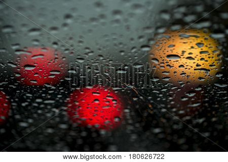 View of the modern city through the window on a very dark stormy night. Concept life of a modern city, urban traffic, night car driving. Abstract background for banner design