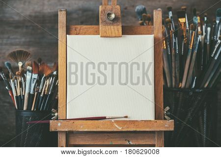 Artistic Equipment In A Artist Studio: Empty Artist Canvas On Wooden Easel And Paint Brushes Retro T