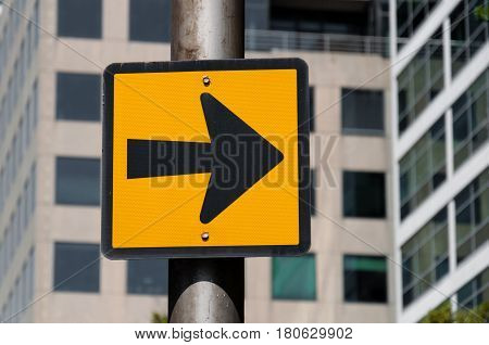 Directional Black Arrow Sign Over Defocused Office Building Background