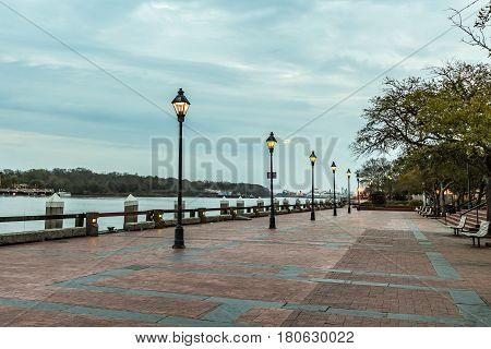 Lamplight illuminates the morning on River Street in Savannah Georgia.
