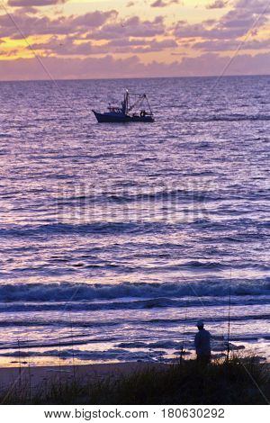 Silhouette of a fisherman fishing trawler on the water surrealistically lit by a sunset in Indian Rocks Florida both ready to head home after a long day of fishing the Gulf of Mexico