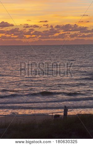Silhouette of a fisherman with fishing pole fishing on a beach along the Gulf of Mexico as he watches a gloriously colorful sunset