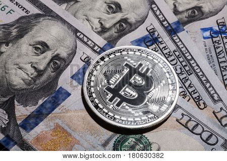One Bitcoin on hundred dollars bills. Closeup, macro shot