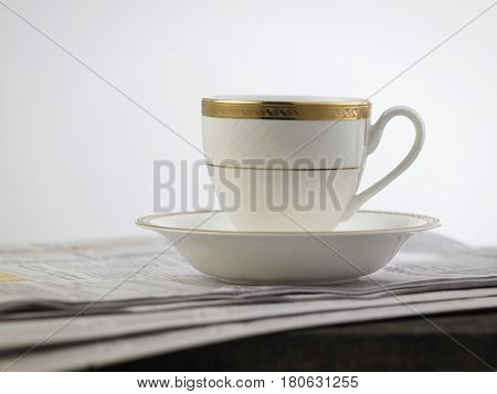 cup with golden liner on the financial newspaper