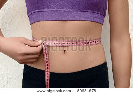 Athletic young woman measuring her waistline with centimeter type. Fitness body.