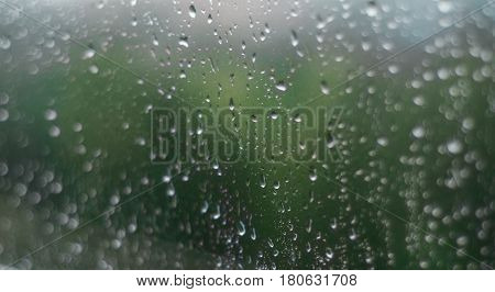 Misted glass, pink purple and golden sparkling champagne rain drops dew drops bubbles on tinted glass window on a rainy day champagne colored sparkling golden rain drops beautiful