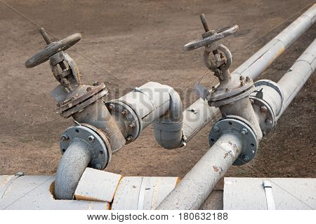 Old made of steel hot water pipes with two valves outdoors