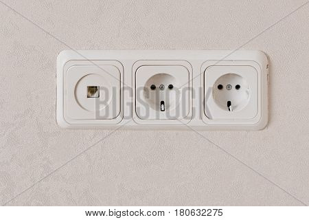 Two electric outlets on wall EU standart and telephone plug, copyspace.
