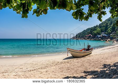 A boat at the white sand beach of the tropical blue sea. Daytime, Haad Yuan, Koh Phangan, Thailand