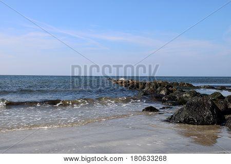 Rocky outcrop sand and sea at a coastal beach