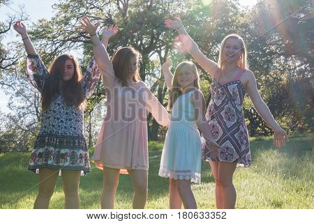 Group of Girls Standing With Arms Raised and Sunlight Overhead