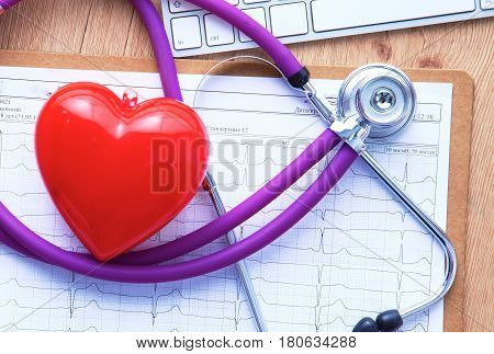A medical stethoscope lies on the patient's medical history on a computer background. The concept of medical care or insurance.
