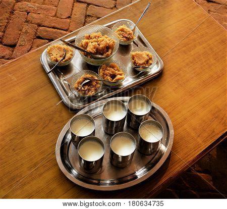 Indian dessert and glasses of milk served in steel utensils.
