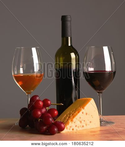 A bottle and a glass of wine on a table with fruit.