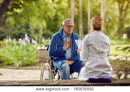 Nurse with elderly man in wheelchair who don't feel good outdoor
