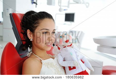 Little girl with a doctor doll in a red dental chair. Pediatrics.