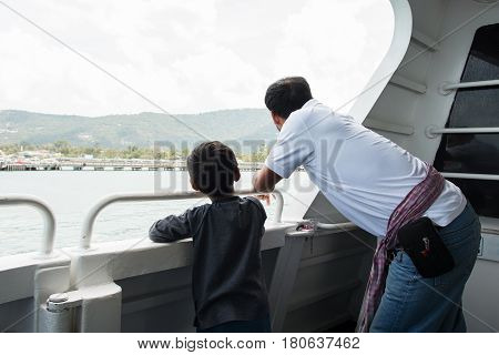 Happy father and his son looking sea on ship