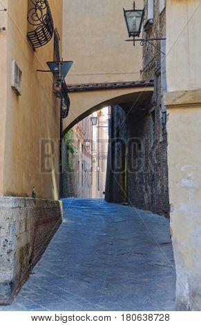 Empty beer bottle left in a winding, quiet, empty alley of Siena, Italy