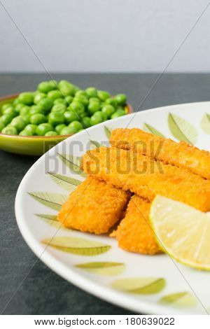 Breaded and Baked Fish Sticks fingers on a plate with a bowl of peas and a slice of lemon