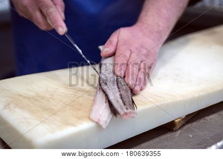 Fish seller short with a thin knife on the market of Cadiz Andalusia Spain