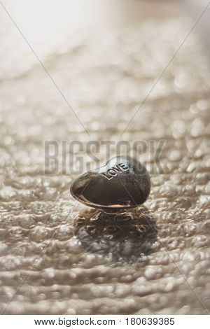 small love heart stone on a bubble wrap it from the back by sun