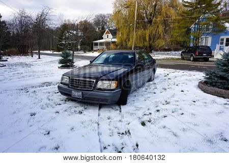 HARBOR SPRINGS, MICHIGAN / UNITED STATES - NOVEMBER 21, 2016: A black 1996 Mercedes Benz S420 luxury sedan is parked in the front yard of a home in Harbor Springs, after a November snowstorm.
