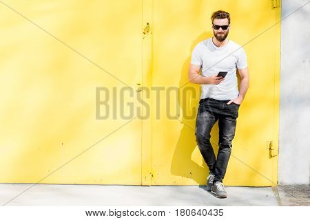 Colorful portrait of a handsome man dressed in white t-shirt and jeans with phone on the yellow background