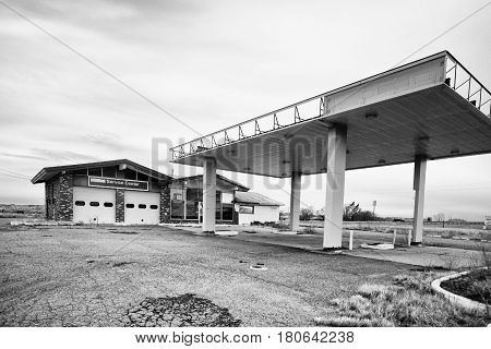 A closed up old gas station with overhead roof and pumps removed service station in black and white