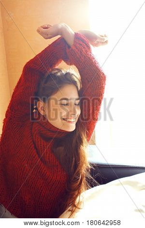 young pretty real woman in red sweater and scarf all over her face smiling at home, winter positive healthy morning