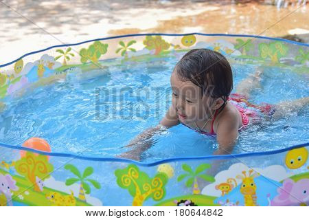 Cute happy baby laughing sitting inside of little plastic bath in the garden on a hot summer day
