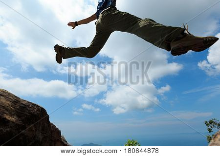 jumping over precipice between two rocky mountains. freedom risk challenge success concept