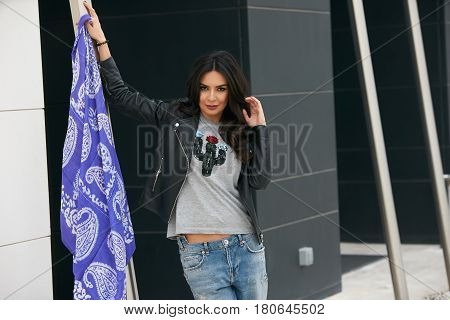 Portrait of Beautiful brunette young oriental beauty female  with black long hair Dressed in Leather jacket and denim pants with Oriental blue scarf and oriental jewelry.