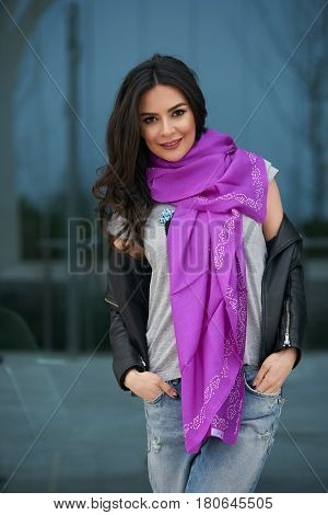 Portrait of Beautiful brunette young oriental beauty female model with black long hair Dressed in Leather jacket and denim pants with Oriental pink scarf and oriental jewelry.
